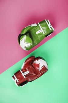 Boxen von grünen und roten handschuhen auf einem rosa und blauen hintergrund diagonal