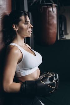 Boxende frau, die mit sandsack, auf dunkelheit aufwirft. starkes und unabhängiges frauenkonzept