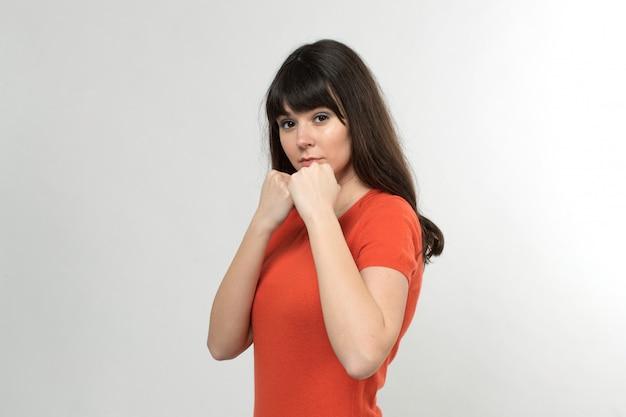 Boxende junge dame, die im boxen steht und in entworfenem t-shirt mit langen haaren auf weiß wartet