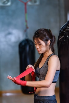 Boxendes asien-mädchen bindet den verband auf ihrer hand