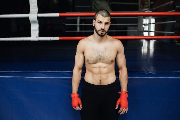 Boxer mit nacktem oberkörper steht in der nähe des rings. hochwertiges foto