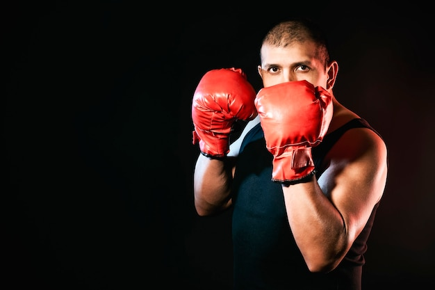 Boxer schaut in die kamera, während er mit boxhandschuhen trainiert
