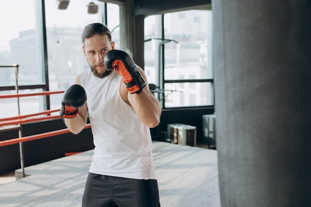 Boxer schlägt boxsack in der turnhalle in der zeitlupe. junger mann, der zuhause ausbildet. starker athlet im fitnessstudio