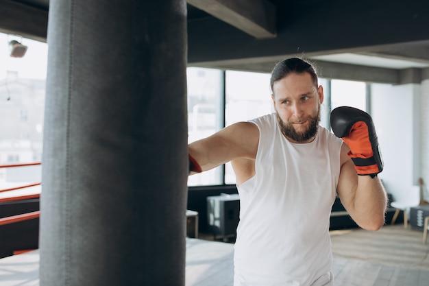 Boxer schlägt boxsack in der turnhalle in der zeitlupe. junger mann, der zuhause ausbildet.