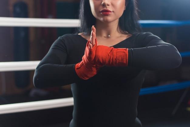 Boxerfrauenhände mit roten boxverpackungen im boxring. nahaufnahme. nahaufnahme hände des weiblichen kämpfers, der boxbandagen-vorbereitung trägt. das konzept der weiblichen macht und männlichkeit. hände klatschen
