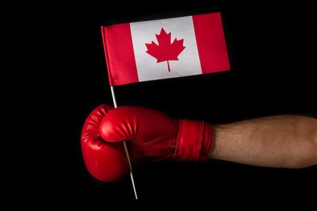 Boxerhand hält flagge von kanada. boxhandschuh mit kanadischer flagge. schwarzer hintergrund.