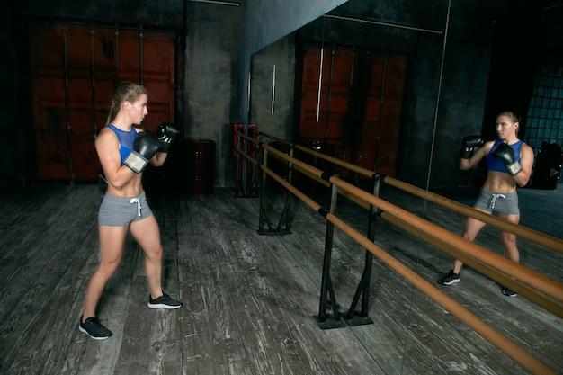 Boxerin steht vor dem spiegel