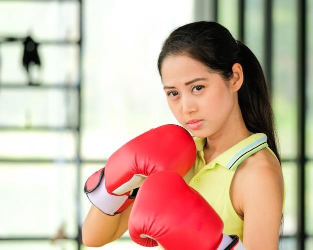 Boxerin trägt rote handschuhe und übungen in der turnhalle.