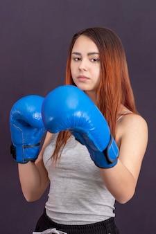 Boxermädchen in den blauen boxhandschuhen in einem grauen t-shirt im gestell