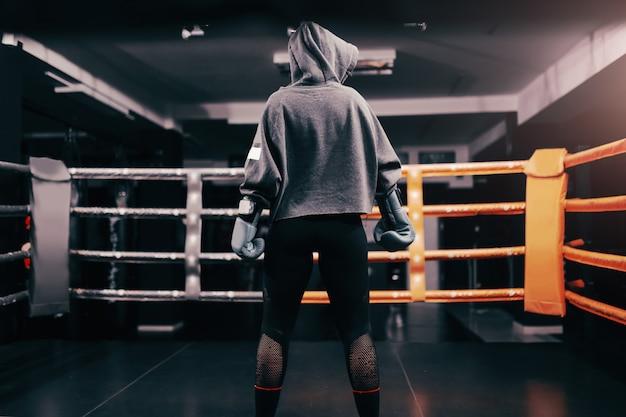 Boxermädchen mit kapuzenpulli und boxhandschuhen auf stehendem ring mit gedrehtem rücken.