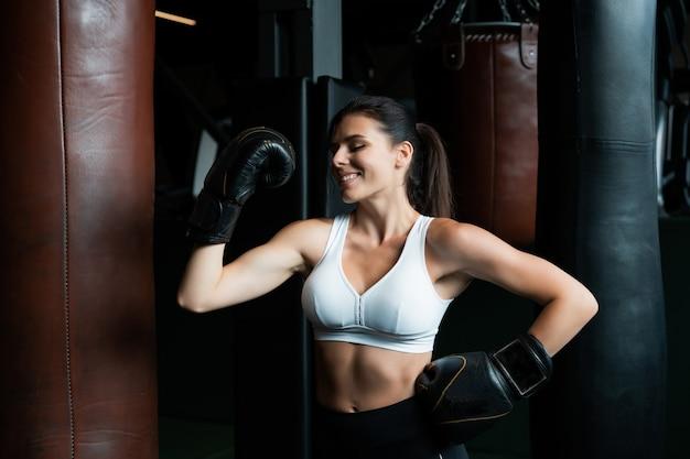 Boxfrau, die mit boxsack auf dunklem fitnessstudio aufwirft. starkes und unabhängiges frauenkonzept