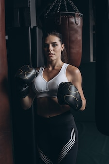 Boxfrau, die mit boxsack auf dunklem hintergrund aufwirft. starkes und unabhängiges frauenkonzept
