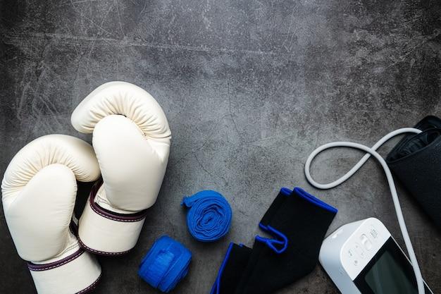 Boxhandschuh blutdruckmessgerät fitnessgeräte auf dunklem hintergrund