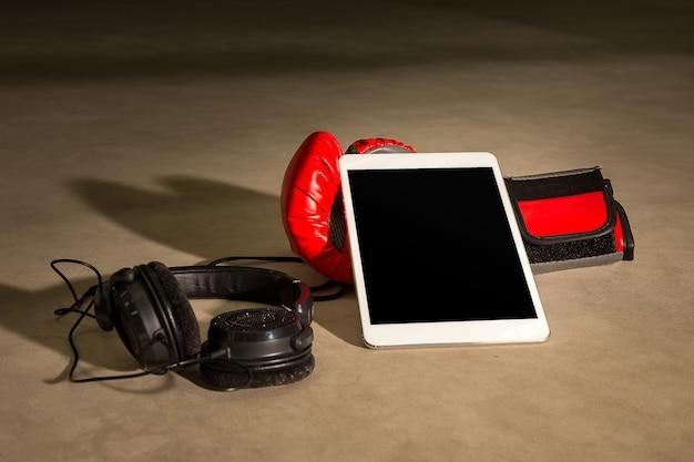 Boxhandschuh mit tablet und kopfhörer für musik hören auf boxin