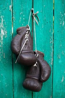 Boxhandschuhe, die an der alten hölzernen wand hängen