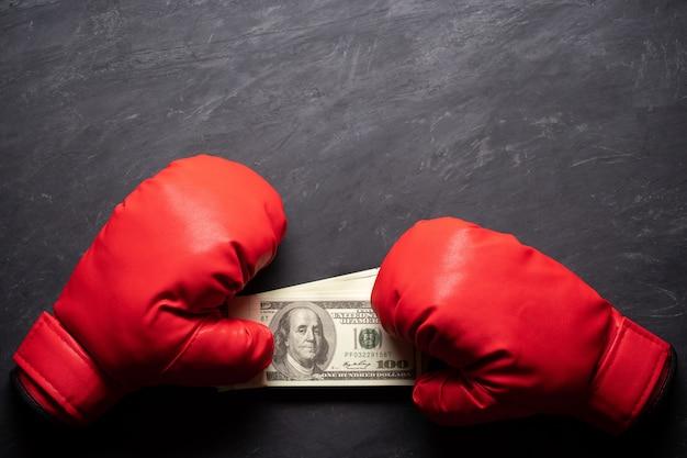 Boxhandschuhe hält die dollarbanknote auf schwarzem zementhintergrund.