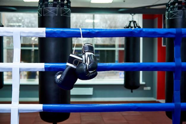 Boxhandschuhe in einem boxring mit taschen in der turnhalle.