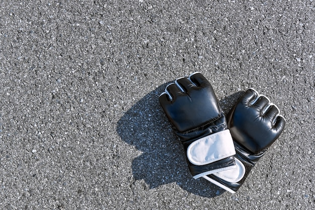 Boxhandschuhe. nahaufnahme der schwarzen handschuhe des sportboxens auf dem asphalthintergrund