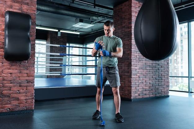 Boxring. hübscher gut aussehender boxer, der sich motiviert fühlt, während er sich auf das training in der nähe des boxrings vorbereitet