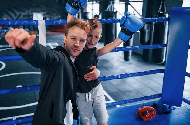 Boxtrainer, der mit jungen im ring steht und gemeinsam den sieg feiert.