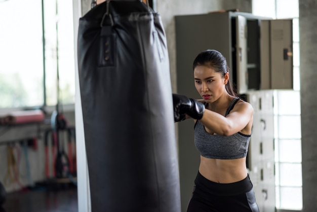 Boxtraining der asiatischen frau durch schieben des sandsacks im fitnessstudio
