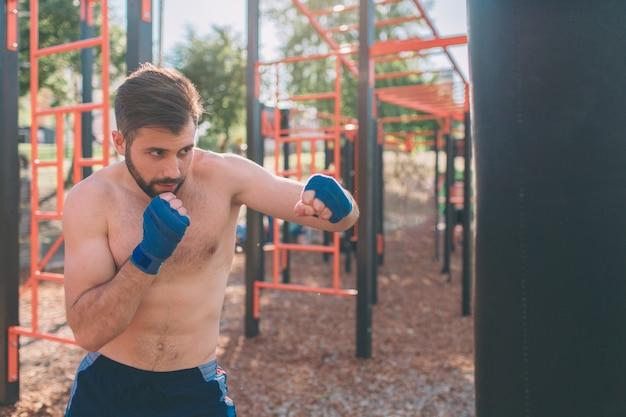 Boxtraining des jungen mannes. boxerübung athletic boxing concept. boxer punsch hand durch boxsack.