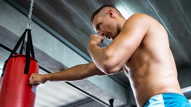 Boxtraining des jungen mannes in der eignungsturnhalle auf unscharfem hintergrund athletischer mann, der starkes s ausbildet