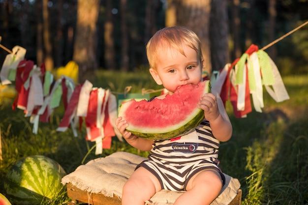 Boy blond sitzt von wassermelonen an einem sommertag umgeben