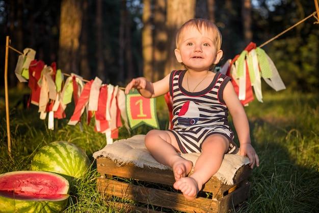 Boy blond sitzt von wassermelonen an einem sommertag umgeben Premium Fotos