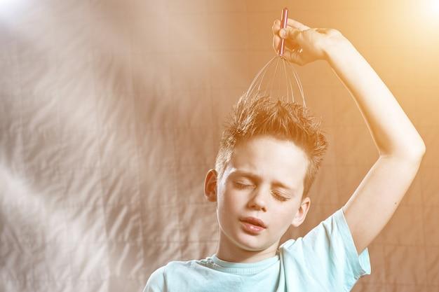 Boy kitzelt seinen kopf mit einem kratzer und bedeckt seine augen mit vergnügen