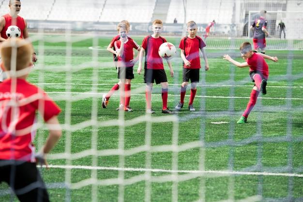 Boy scoring goal während des spiels