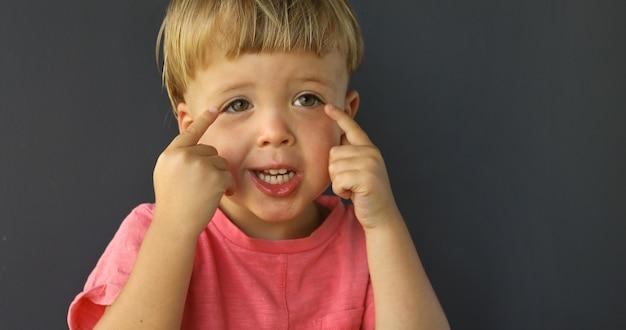 Boy zeigt mit beiden händen auf seine augen