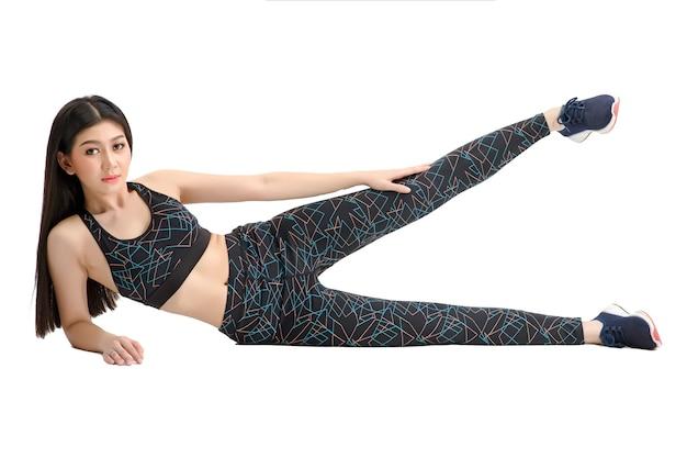 Bräune haut. asiatisches fitness-mädchen in sexy niedlichen sport-bh schwarze spandex-hose übung zum aufwärmen. üben von übungen für die hüften und oberschenkel. durch isolierten weißen hintergrund.