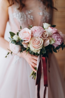 Bräute, die blumenstrauß mit pfingstrosen, freesie und anderen blumen in den händen der frauen heiraten. licht und lila frühlingsfarbe. morgen im zimmer