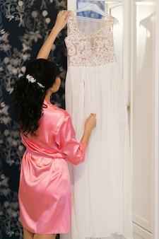 Bräute morgenvorbereitung. frau im rosa bademantel, der hochzeitskleid hält