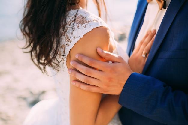 Bräutigam berührt sanft die hand seiner frau