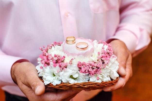 Bräutigam, der blumenblumenstrauß mit zwei eheringen hält