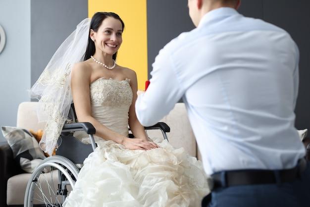 Bräutigam, der braut im rollstuhl ring gibt. hochzeit für menschen mit behinderungen konzept