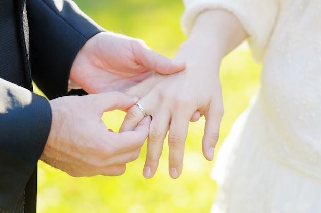 Bräutigam, der einen ehering auf den finger der braut setzt
