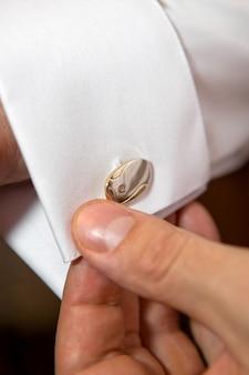 Bräutigam, der manschettenknöpfe anlegt, während er in der formellen kleidung nah oben angezogen wird