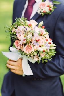Bräutigam, der rosenblumenstrauß, abschluss hochhält