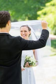 Bräutigam, der seine braut im park enthüllt