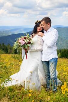 Bräutigam, der seine junge frau in den bergen umfasst.