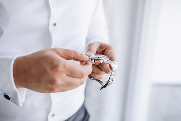 Bräutigam, der zeit auf seiner armbanduhr überprüft