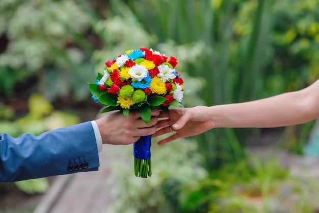 Bräutigam gibt der braut einen hochzeitsstrauß