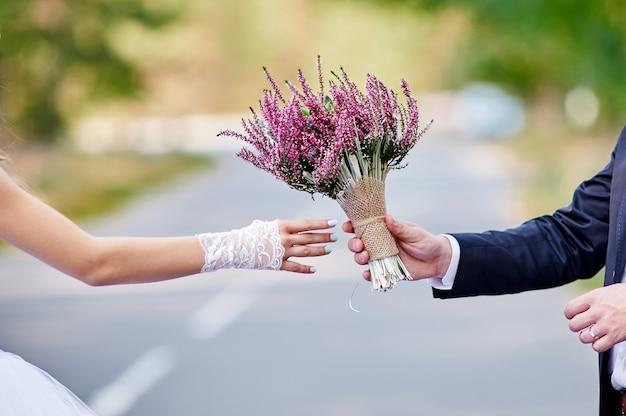 Bräutigam gibt der braut einen schönen hochzeitsblumenstrauß
