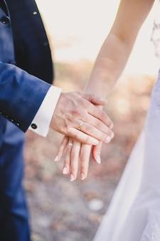 Bräutigam hält brauthand im weißen kleid.
