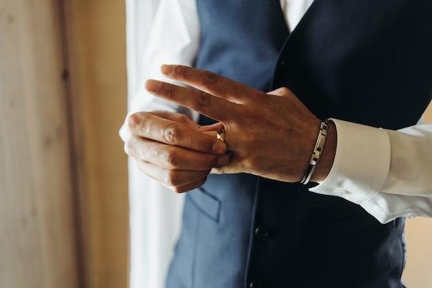 Bräutigam hält den ehering, der vor dem fenster in einem hotel r steht