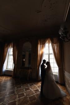 Bräutigam hält die braut in einem luxuriösen zimmer mit großen fenstern und spiegelprofil