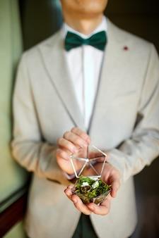 Bräutigam hält eheringe in dekorativer handgemachter rustikaler box mit pflanzen